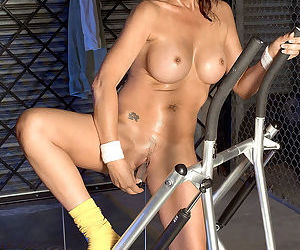 Brunette mature babe with fake jugs Desi Foxx masturbates nice in the gym