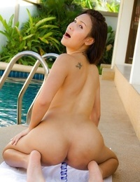 Young ladyboy Oil removes her bikini in pool and flashes ladyboy pussy