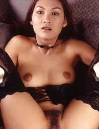 Sexy asian babe in stockings and lingerie showing off her titties and bush
