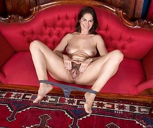 Mature woman Kaysy spreads her hairy cooter wide open on velvet loveseat