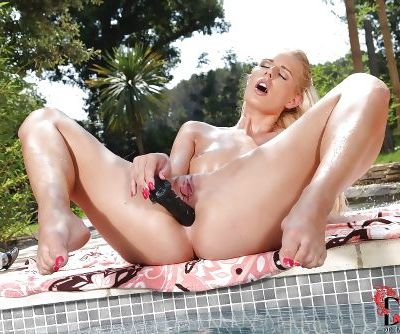 Graceful blonde floosie has some anal fun with a black dildo outdoor