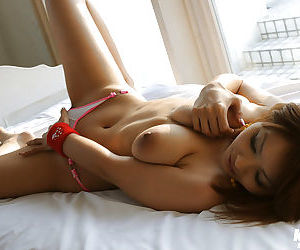 Amateur asian babe with massive tits stripping and posing naked on the bed