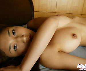 Sweet asian girl with big tempting knockers posing naked on the bed