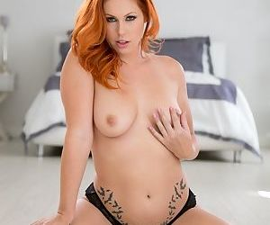 Redhead female Edyn Blair takes off her bra and panties to model naked