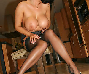 Classy brunette vixen shows her great breasts as she teases in black stockings and slutty high heels.