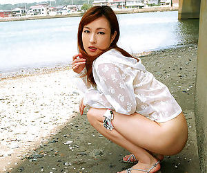 Cute asian babe with neat ass stripping and spreading her legs