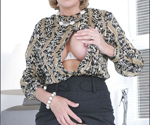 Mature lady in formal suit revealing her big jugs and ample ass
