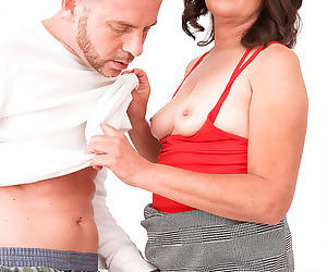 Mature lady Kelly Scott gives a blowjob after being partly undressed by a man