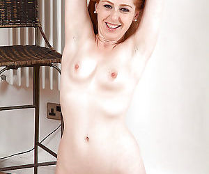 Older redhead Tia Jones parting bare legs to display really hairy pussy