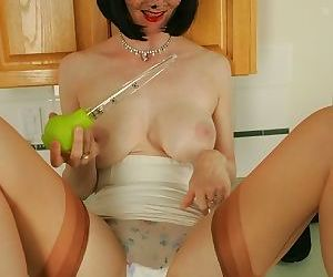 Busty mature lady in stockings posing topless and teasing her pussy