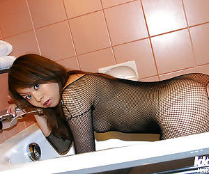 Slim asian babe with tiny tits posing in pantyhose suit in the bath