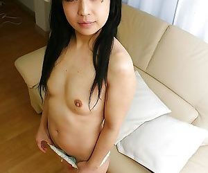 Shy asian chick in black pantyhose getting rid of her clothes
