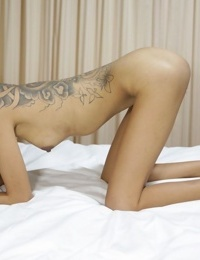 Skinny Thai girl with tattoos and braces makes her nude modelling debut