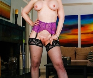 Mature lady Nina Hartley wears glasses while flaunting her big tits in nylons