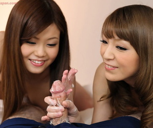 Two Japanese girls jerk off a cock and eat sperm together