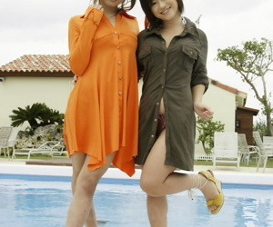 Japanese teens model with their clothes on at side of swimming pool