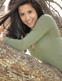 Latina chick Bella Quinn climbs a tree in the park wearing a sweater and jeans