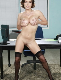 Busty business woman Krissy Lynn smilingly strips to pose naked on her desk