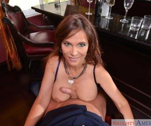 Middle-aged American female Syren De Mer bangs a man inside a bar