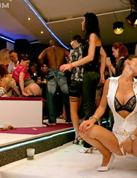 Clothed females have sex with other women and men inside a swingers club