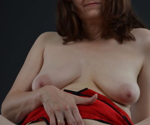 Mature amateur with bare legs uncovers saggy boobs before masturbating