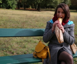 Older woman munches on a loaf on an outdoor bench after getting fucked hard