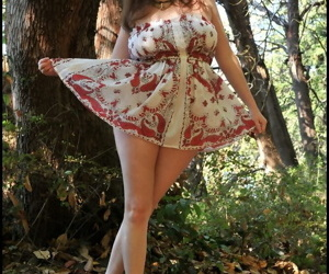 Curvy mature woman Tasty Trixie twerks her booty while disrobing in the woods