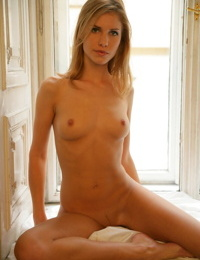 Erotic model Iveta B posing naked in the window to reveal her firm small tits