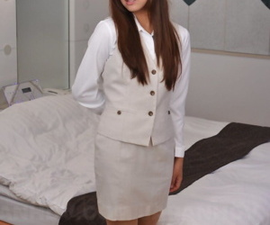 Clothed Japanese woman Nao Yuzumiya cracks a smile in a miniskirt