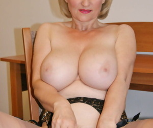 Hot older lady uncups her large tits before toying her twat in tan nylons