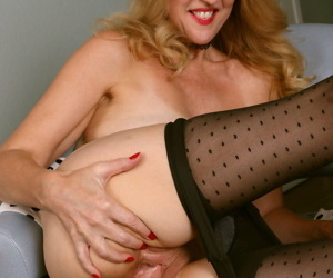 Classy older lady Lacy F rolls off polka dot pantyhose to finish getting naked