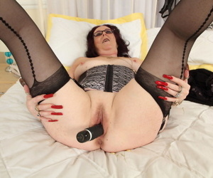 Older British woman with long fingernails sticks a sex toy in her bald pussy