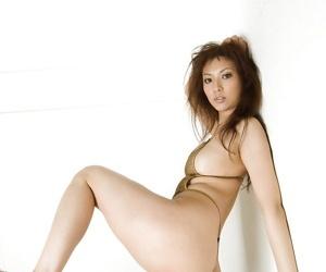 Seductive asian babe on high heels slipping off her bikini