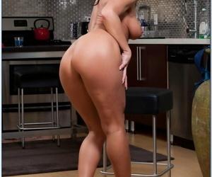 Mature housewife Sarah Bricks cooking something hot in kitchen