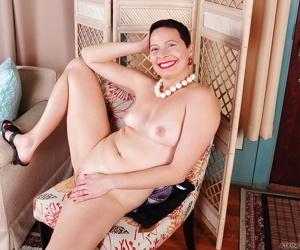 Short haired mature dame Kali Karinena stripping down to underwear