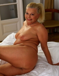 Talkative ash-blonde granny Betsy B doffs undergarments & models her thick tits on the bed